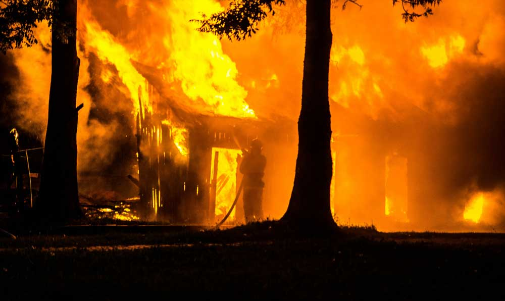 Photograph of a house engulfed in flames.